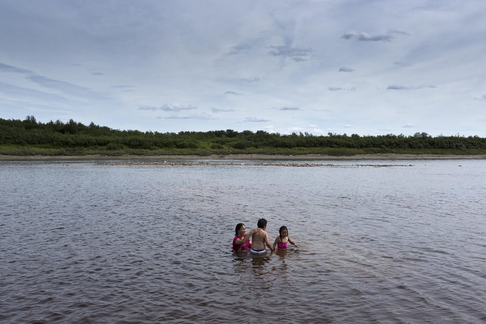 'People of the Parting Rocks' for The Pulitzer Centre on Crisis Reporting . An Auntie swims with her niece and nephew in the Attawapiskat river in Attawapiskat, Ontario.