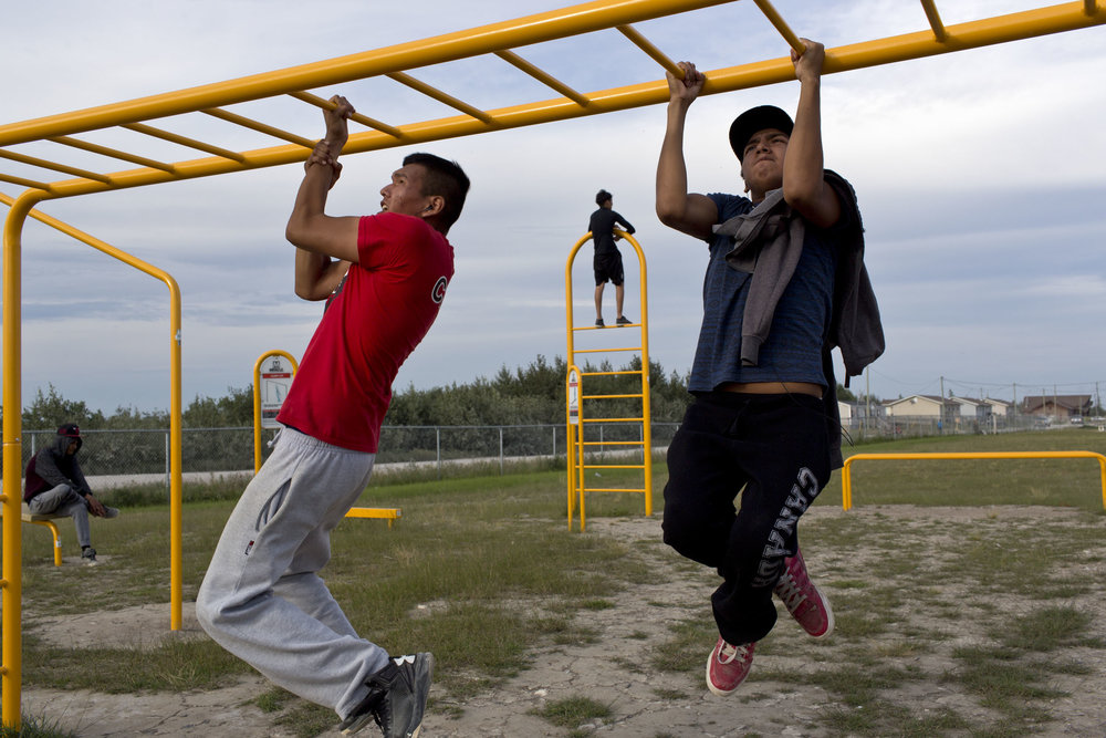 'People of the Parting Rocks' for The Pulitzer Centre on Crisis Reporting . Young men exercise at an outdoor gym in Attawapiskat, Ontario.