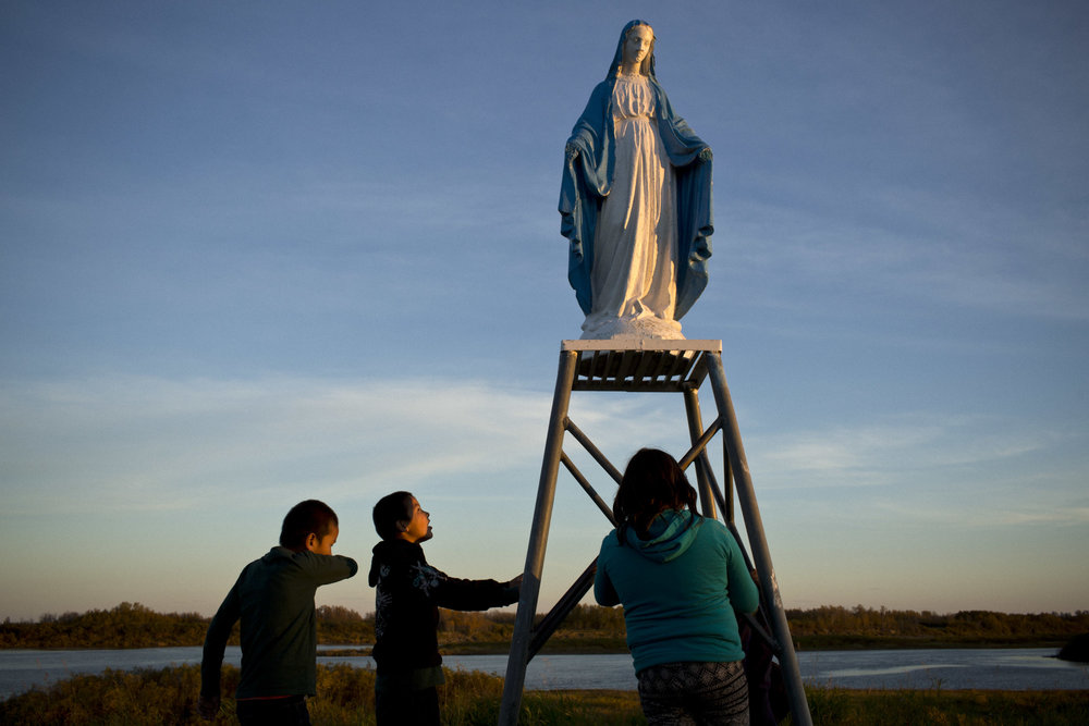 'People of the Parting Rocks' for The Pulitzer Centre on Crisis Reporting . Children play near a statue of the Virgin Mary in Attawapiskat, Ontario.