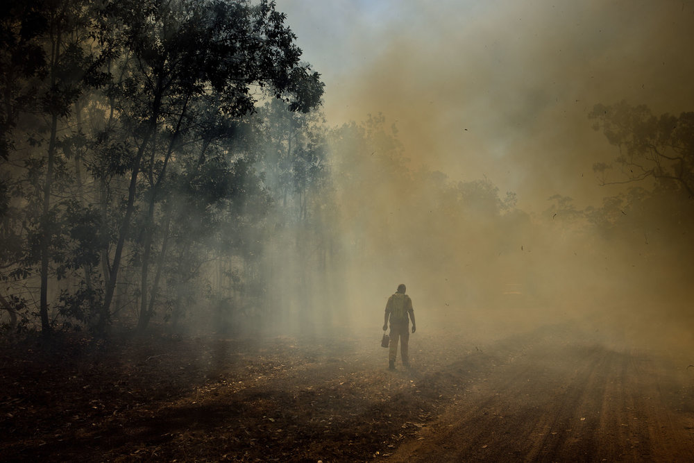A firefighter walks through smoke from a controlled bushfire on Melville Island, Northern Territory.