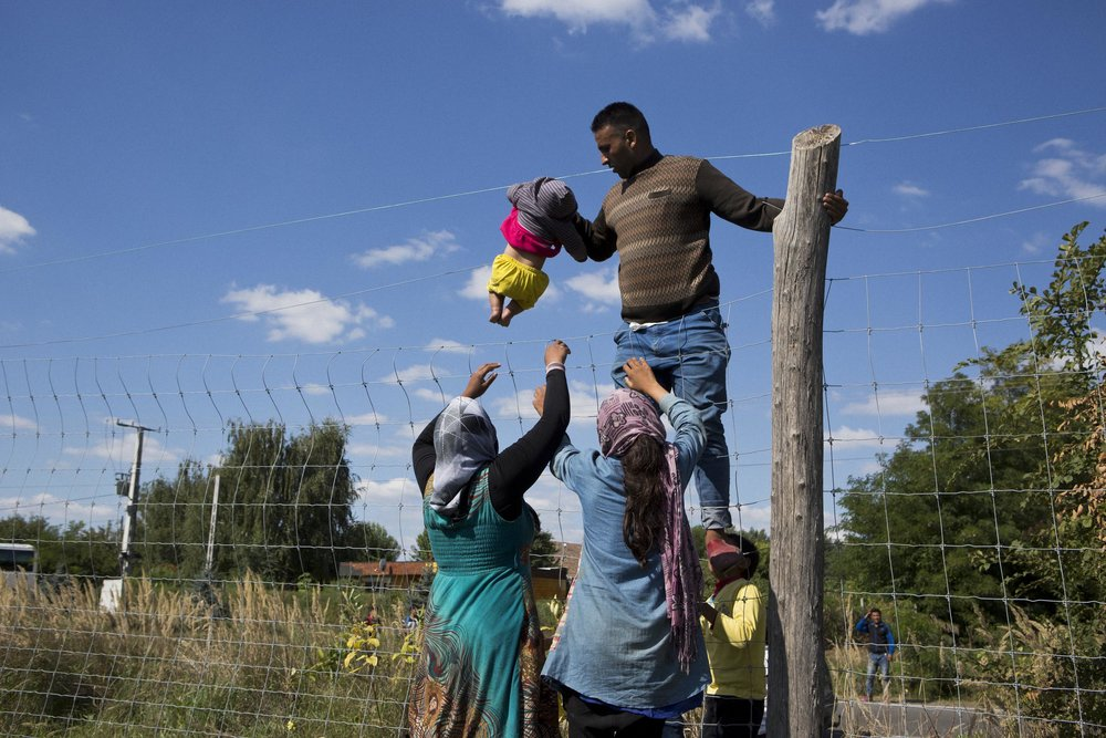 Röszke, Hungary. Refugees lift a baby over a fenceline while trying to evade policenear the Hungary/Serbia border.