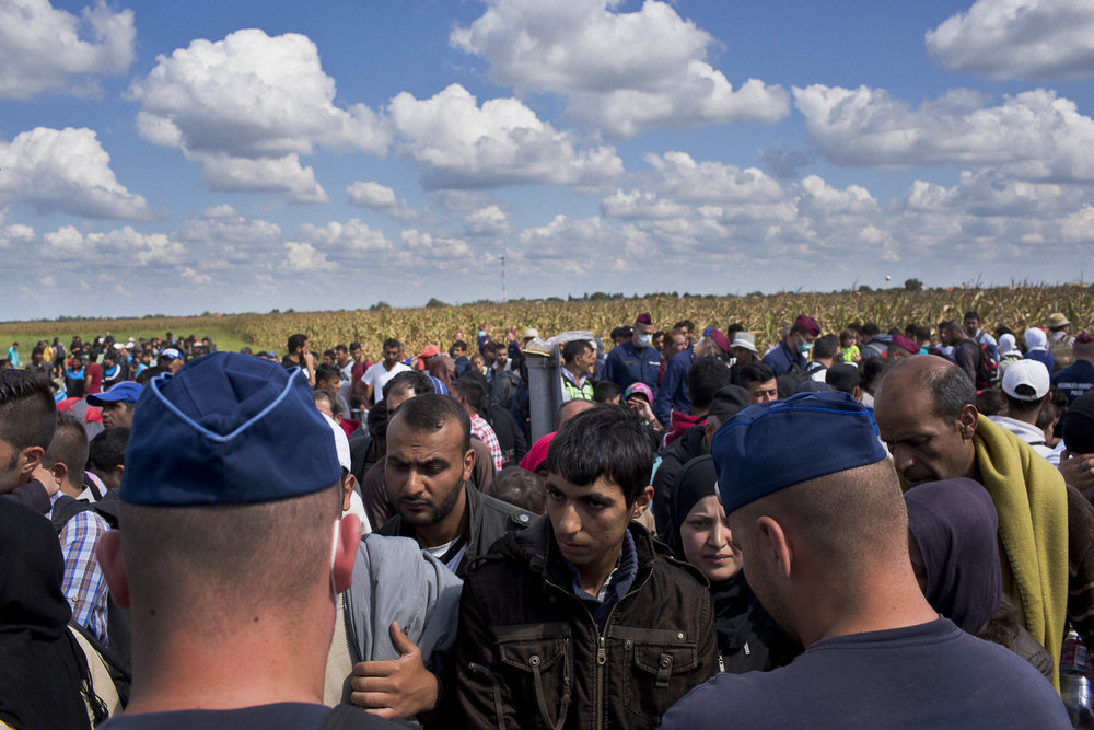 Rözske, Hungary. Refugees wait to board buses bound for processing centres on the Hungarian side of the Serbia/Hungary border.