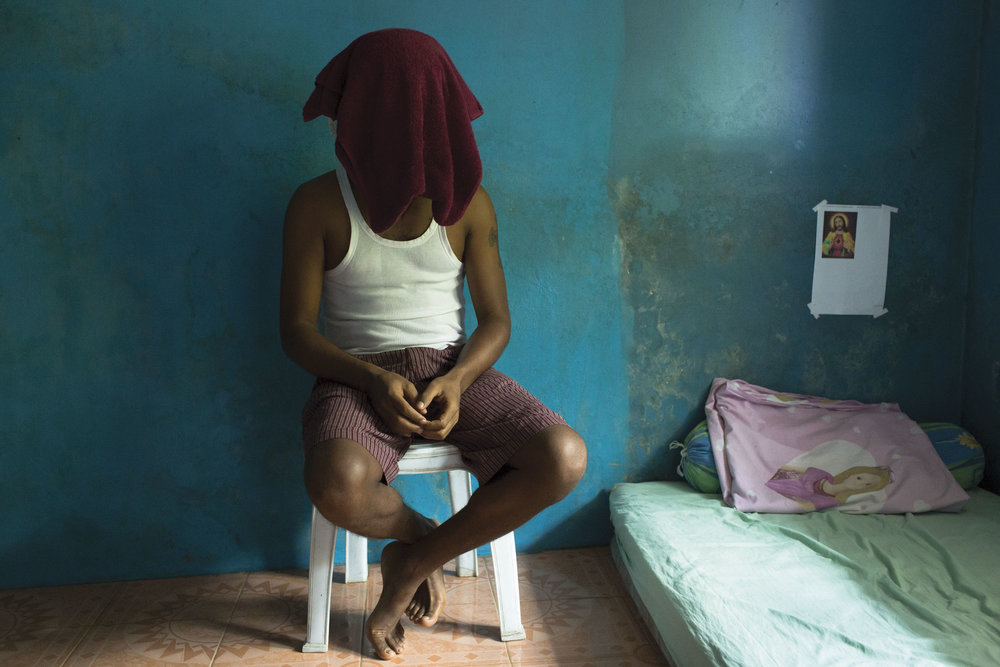 Cisarua, West java, Indonesia. An Eritrean asylum seeker in Cisarua, sits for a portrait while hiding his identity.