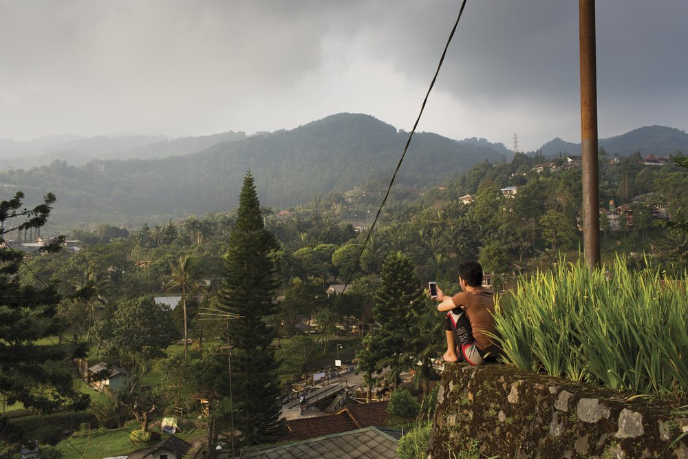 Cisarua, West java, Indonesia. A Hazara asylum seeker skypes with his family at home from a lookout in Cisarua.