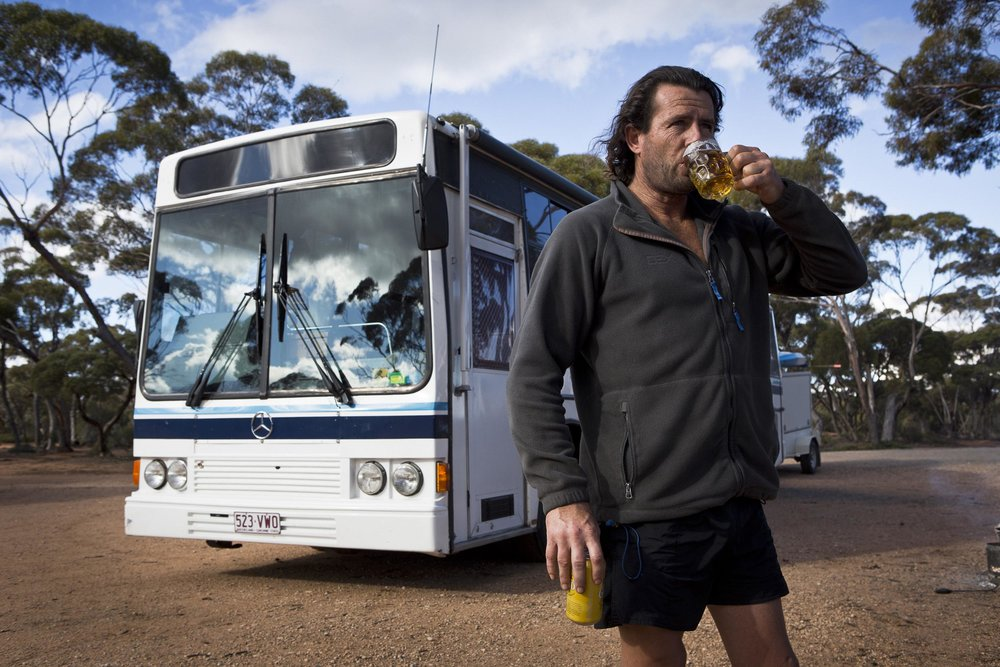 "Jason McIntosh and his bus named ""the Strawberry Cow"", Balladonia, Western Australia."