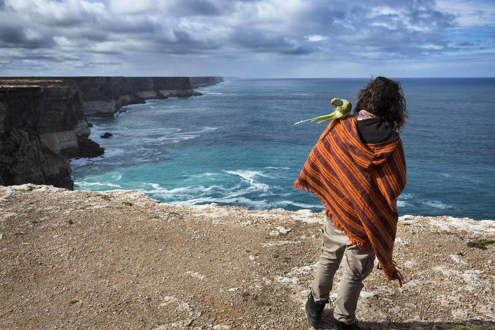 "Jeremy Burrows and his parrot ""Thoth"" at the Great Australian Bight, South Australia, Australia."
