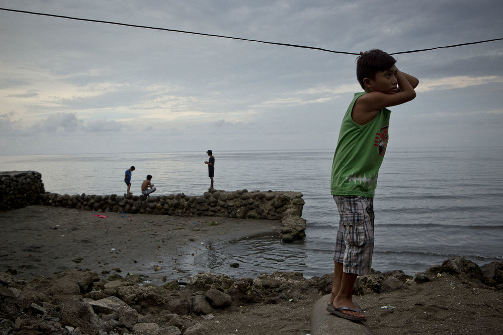 Abdul Wahid Rasheed (aged 8 years) stands near the ocean behind the Buru-un gymnasium IDP centre in Iligan City. Abdul has lived there with his three siblings and parents since May 26, 2017 when fighting broke out in his home of Marawi.