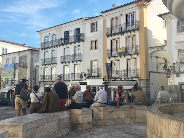 Local residents and tourists sitting on the fountain area in the middle of the square in Evora, Portugal