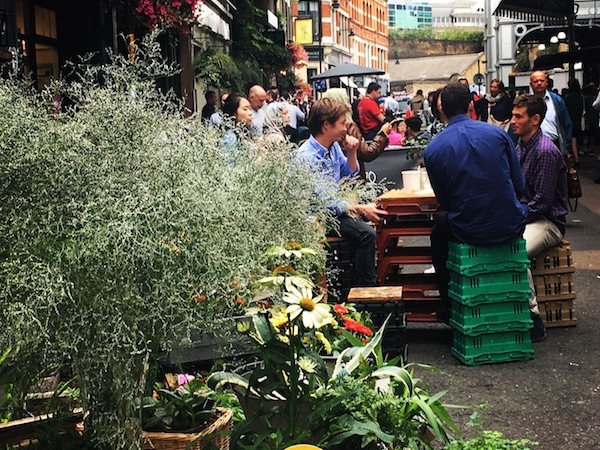 People sitting on plastic boxes in Borough market