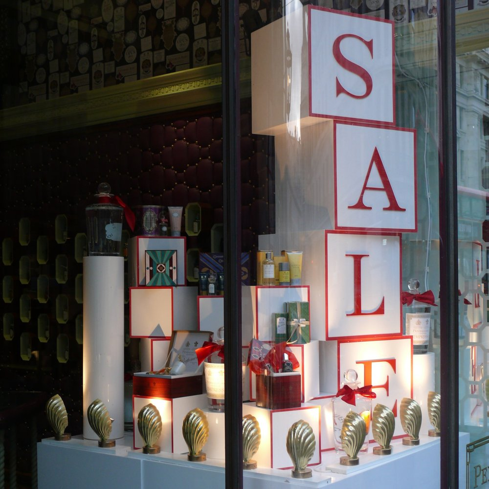 Sale boxes stacked on top of each other with gold shell lights and smaller red and white boxes