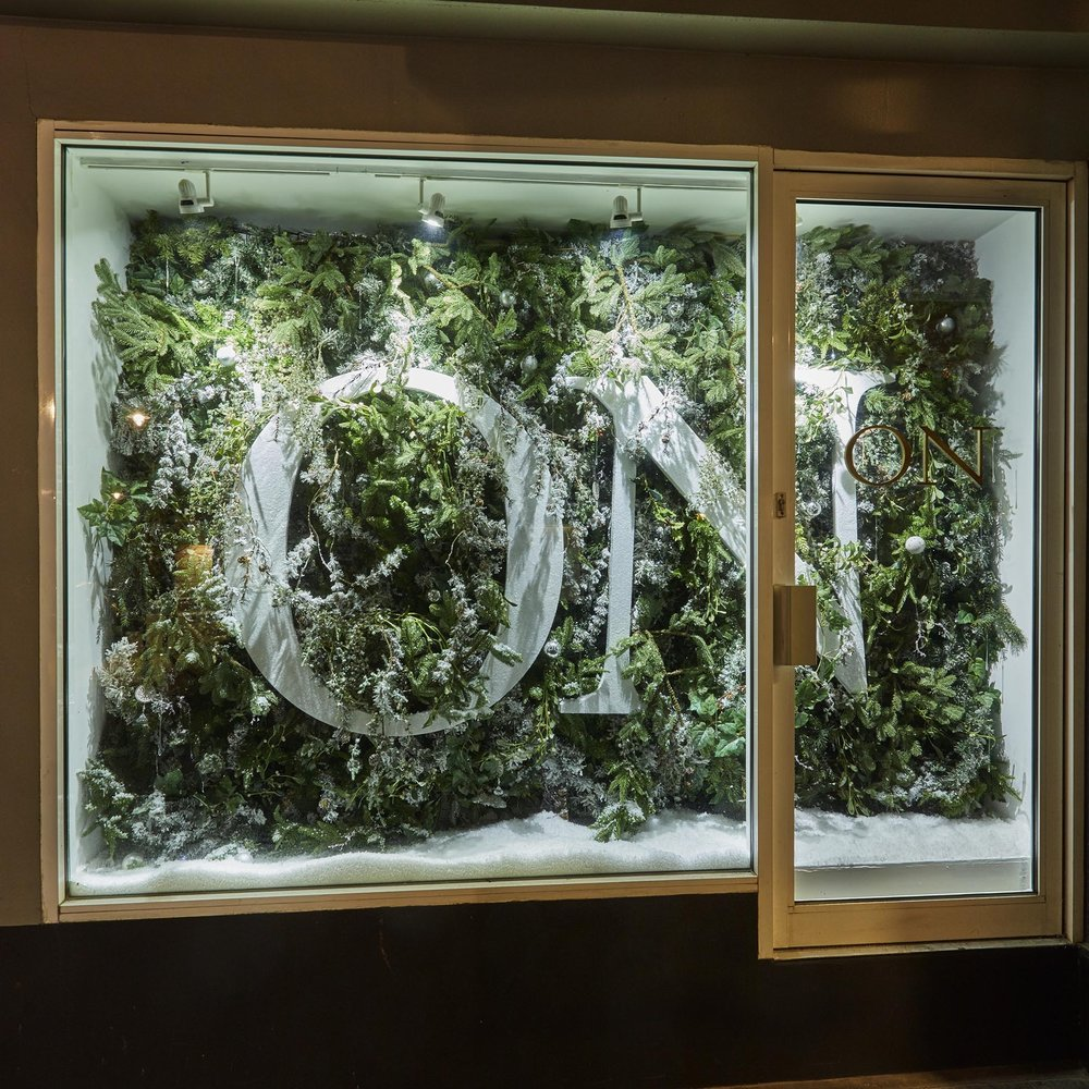 Overgrown foliage window display with glitter letters