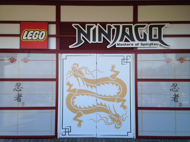 Ninjago signage on red and white building with golden Chinese dragon