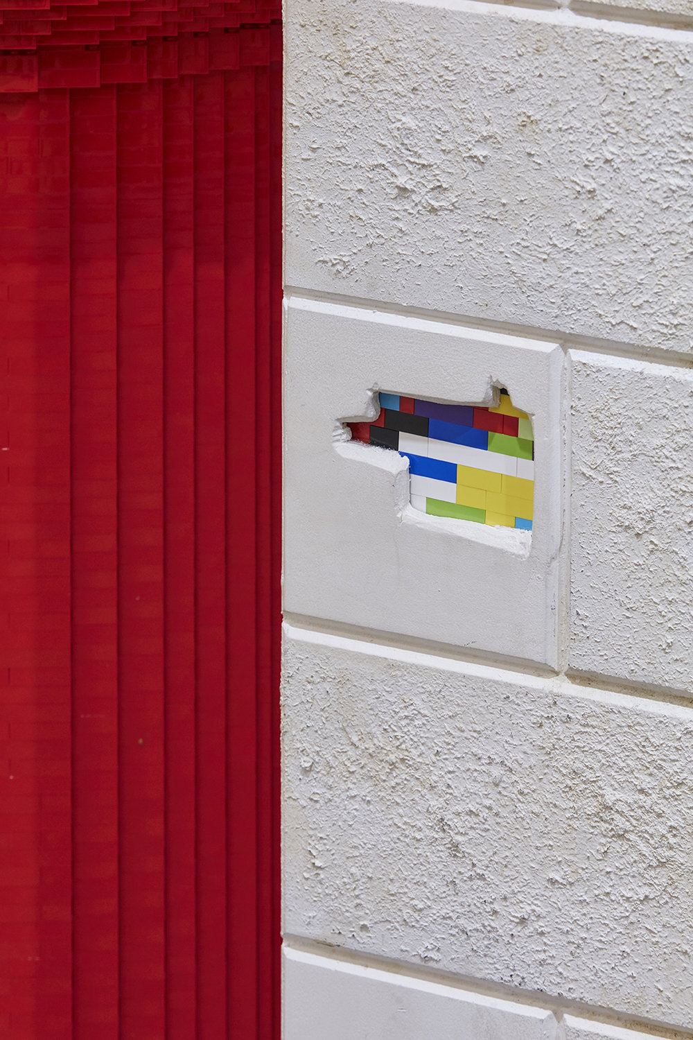 False wall cladding with some chipped away revealing LEGO bricks
