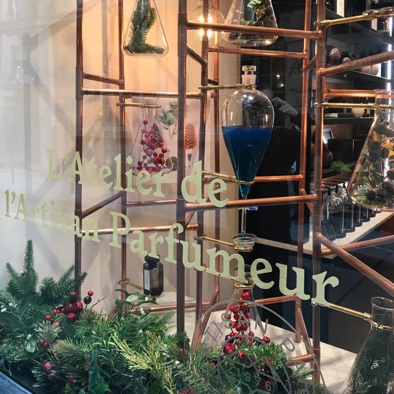 L'Artisan Parfumer Christmas window display with foliage, the heritage scheme and botanical filled conical flasks