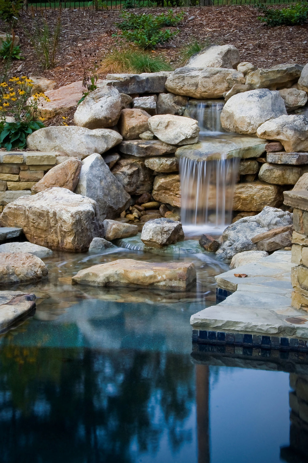Waterfall With Stream Crossing: This beautifully-designed feature also acts as a water delivery system for the pool.