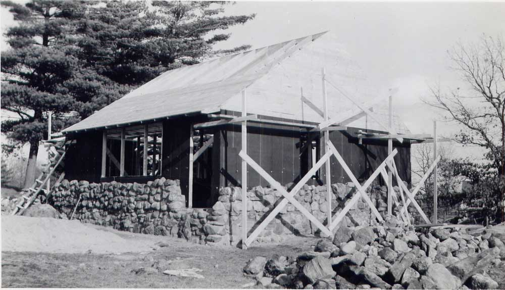 Building the fourth cottage, wood frame and cobblestones going up, 1950.