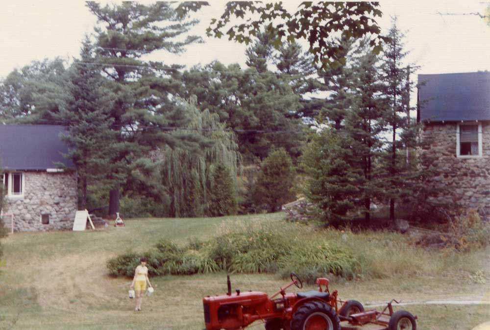 The once denuded landscape now has a groomed lawn, several gardens, and mature trees of maple, oak, willow, cedar and pine varieties, ca 1975.
