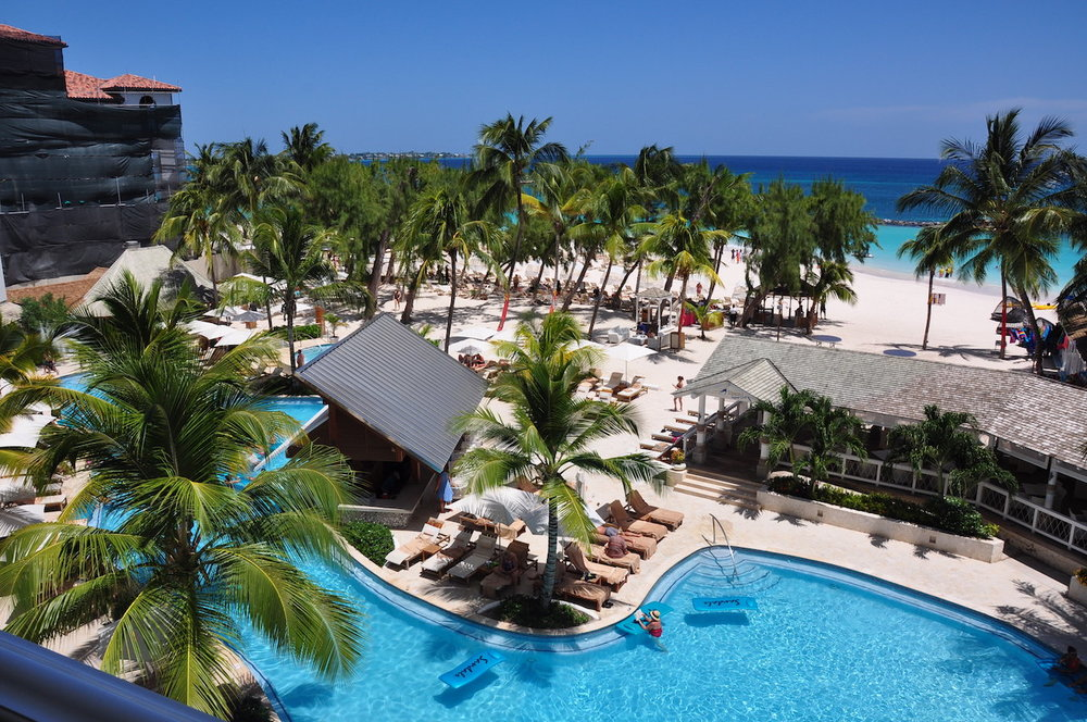 "Sandals Barbados - Travvy Award Winner - Caribbean's Leading Resort 2019: Sandals BarbadosSandals Barbados is built on 7 acres of land located at the water's edge of Maxwell Beach. It is a short 15 minutes from Grantley Adams International Airport. The St. Lawrence Gap area, known for its restaurants, nightlife, and shopping is a 5-minute cab ride away. Like jazz? This is the island for you!The main pool is located in front of the Beachfront Village overlooking the Caribbean. This is where the party is! You will certainly enjoy the beautiful swim-up bar, music, and action! The quiet pool is built in a European style pool behind the Beachfront Village surrounded by red and white cabanas and lush greenery. The Café de Paris is directly behind the quiet pool and we like to stop in for a cappuccino to sip on while lounging. Should you choose the Crystal Lagoon Village as your accommodation, you will have the opportunity to enjoy one of the balcony or infinity edge swim-up lagoon pool suites. Bliss!Sandals Royal Barbados was built right next door, giveing you the opportunity to ""stay at one and play at two"" 5 Star luxury all Included resorts covering 21 acres of beautiful Barbados.Did you know that lobster is always in season in Barbados? Make sure you check to see about that! MORE PICTURES ->"