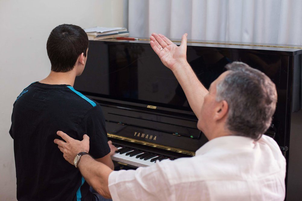 music teacher encouraging boy pianist.jpg