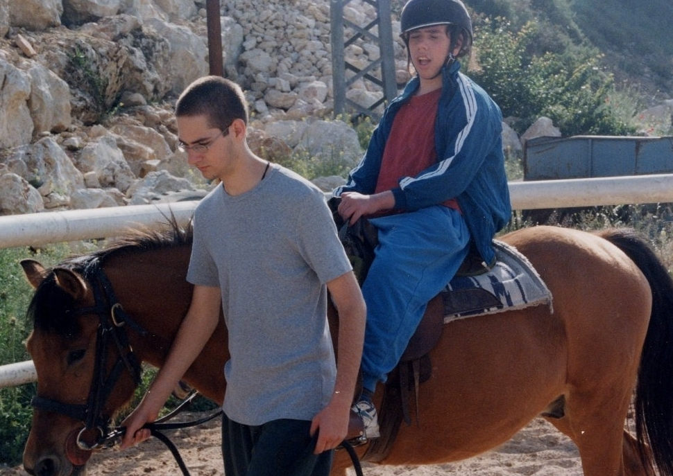 IASA student leading horse carrying his blind and autistic charge.