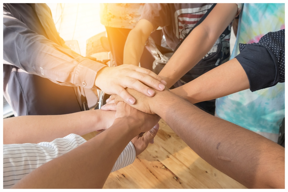 Group of people with hands together before team building event