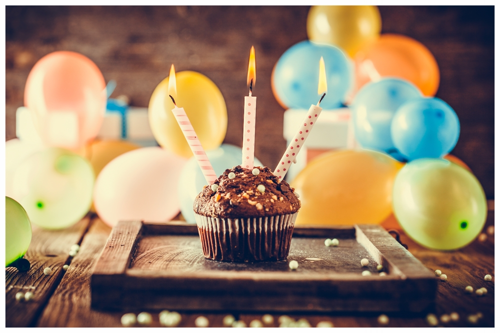 Chocolate birthday cupcake with 3 candles and balloons