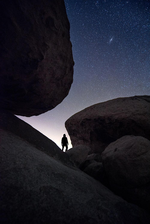 austin-trigg-joshua-tree-national-park-hiker-explores-rocks-night-sky-stars.jpg