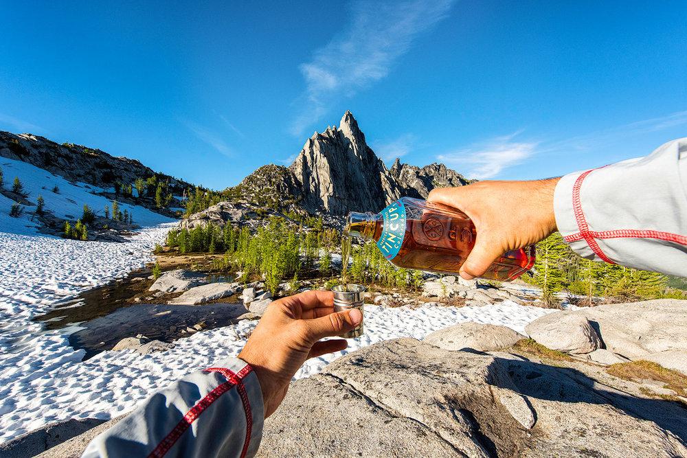 austin-trigg-whiskey-enchantments-washington-product-pour-bottle-shot-mountain.jpg