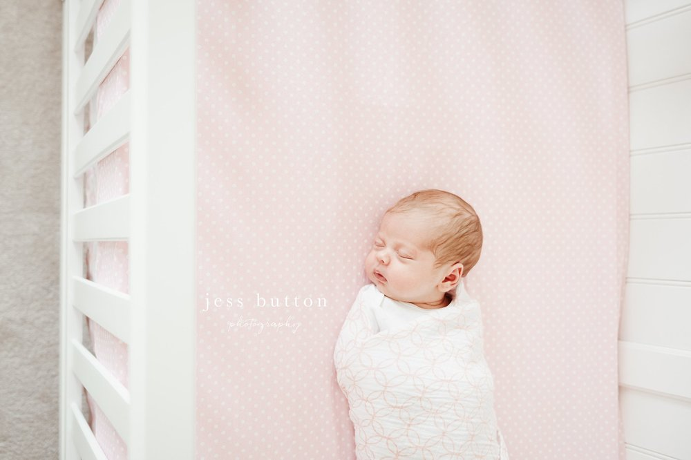 baby girl in crib with pink sheets swaddled