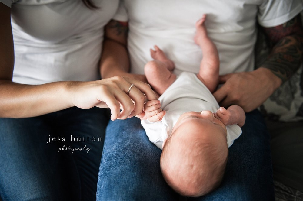 newborn holding mom's hand with ring