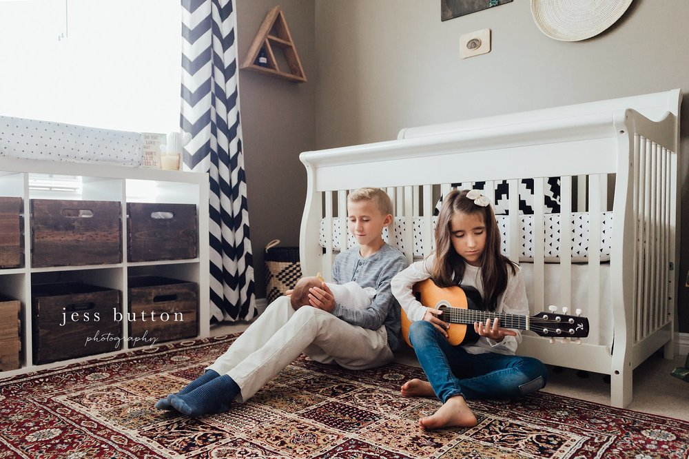 girl playing guitar for newborn brother beside crib