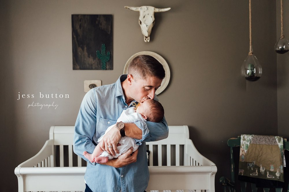 new dad holding newborn and kissing baby's head