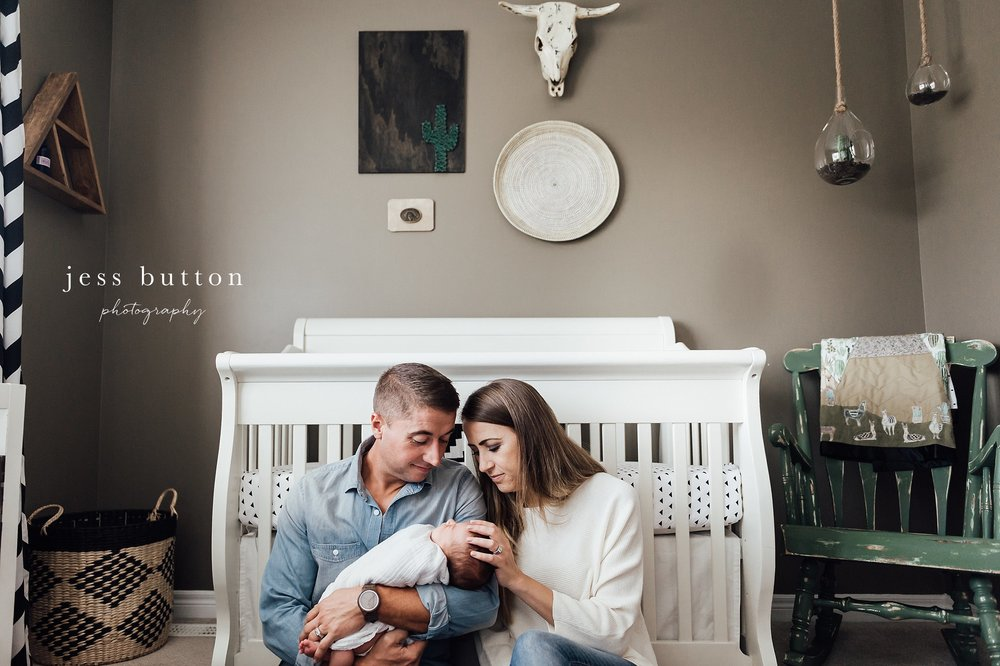 new mom and dad loving baby boy sitting beside crib