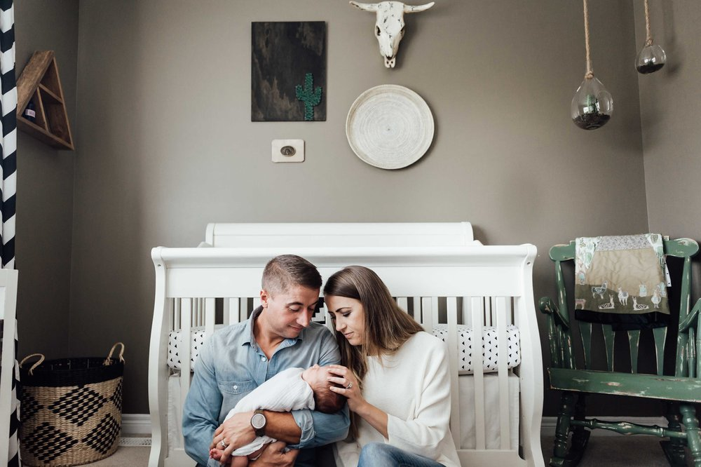 dad holding new baby boy in nursery with mom - St Catharines newborn photographer