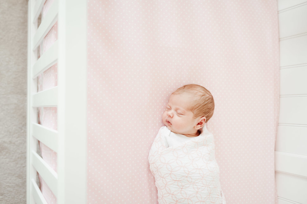 swaddled baby in crib with pink sheets - Niagara Falls newborn photography