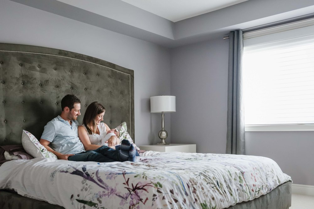 parents holding new baby girl in master bedroom - Fonthill newborn photographer