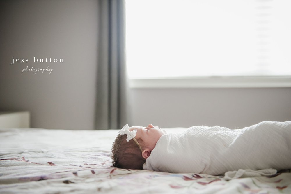 swaddled baby on bed in front of window - Fonthill - Niagara Newborn Photography
