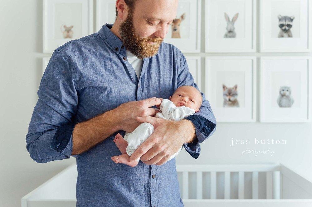 dad holding baby's hand in grey nursery with animal prints - Niagara newborn photographer