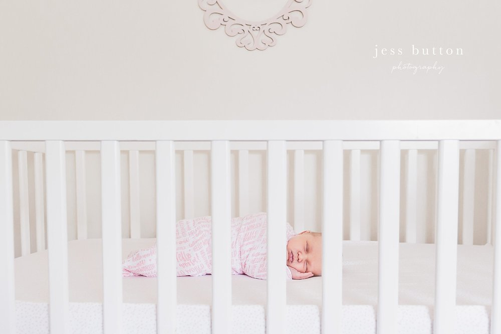 niagara newborn lifestyle photographer - St Catharines baby photos - 8 day old girl in crib  at home swaddled with pink and white blanket