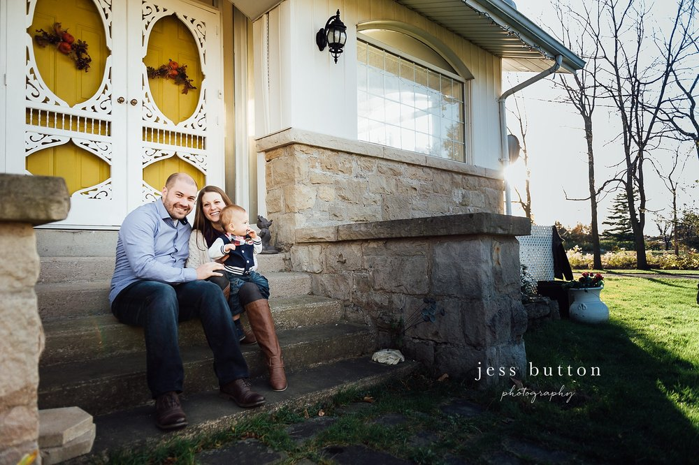 Niagara Family Photographer - photos at home in St Catharines - portrait family of 3 on front porch in front of yellow door