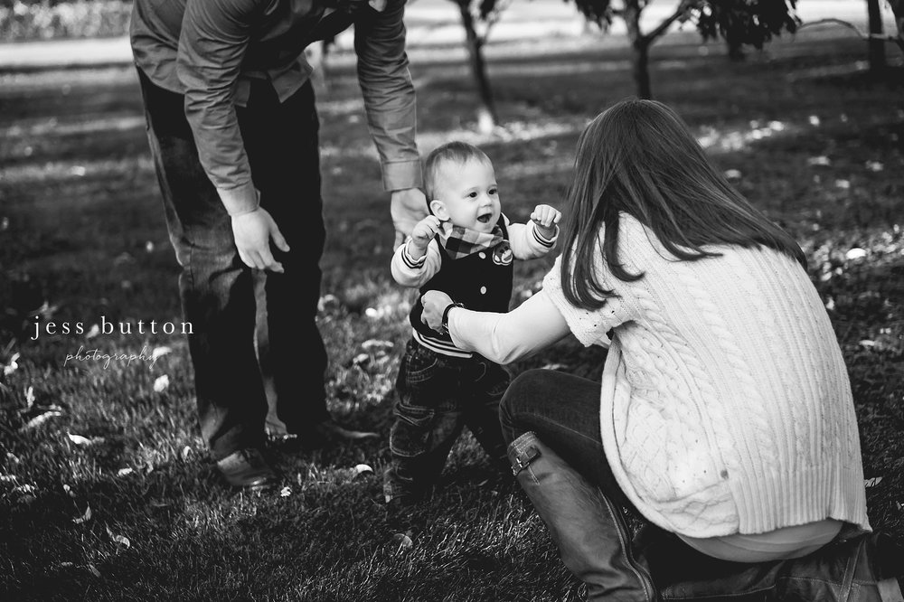 Niagara Family Photographer - photos at home in St Catharines - parents with 10 month old baby boy learning to walk in field