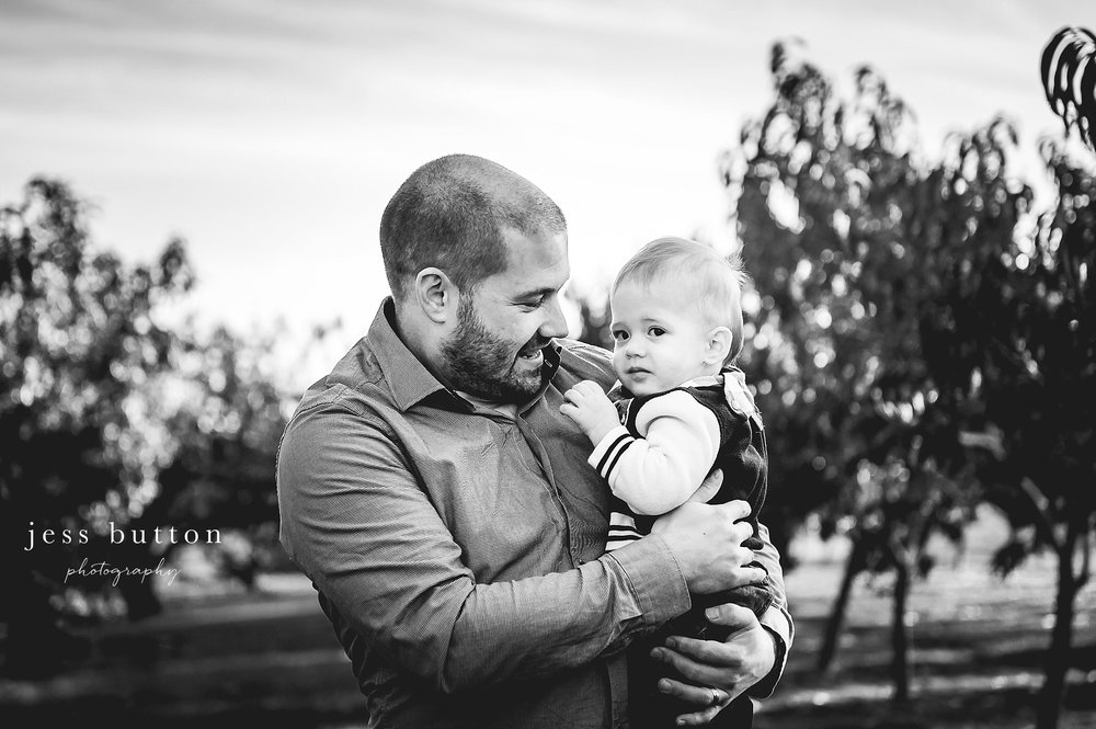 Niagara Family Photographer - photos at home in St Catharines - dad holding10 month old baby boy in orchard