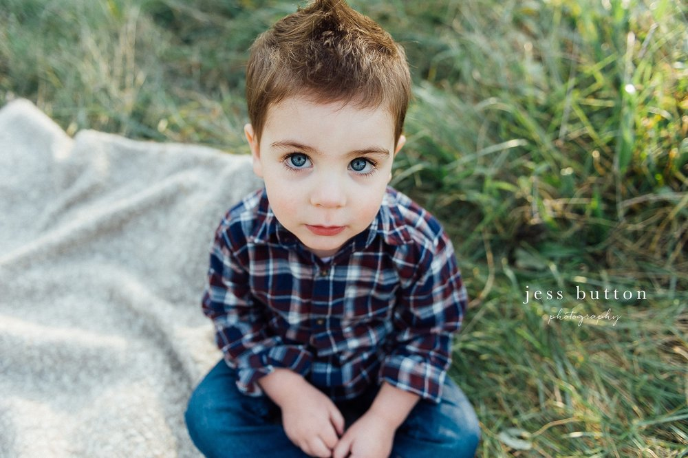 Niagara Family Photographer - Fall family portraits Niagara-on-the-Lake - two year old boy sitting in field