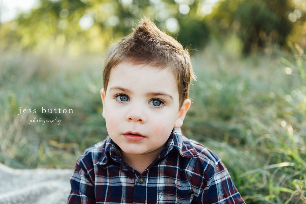 Niagara Family Photographer - Fall family portraits Niagara-on-the-Lake - two year old boy sitting in field