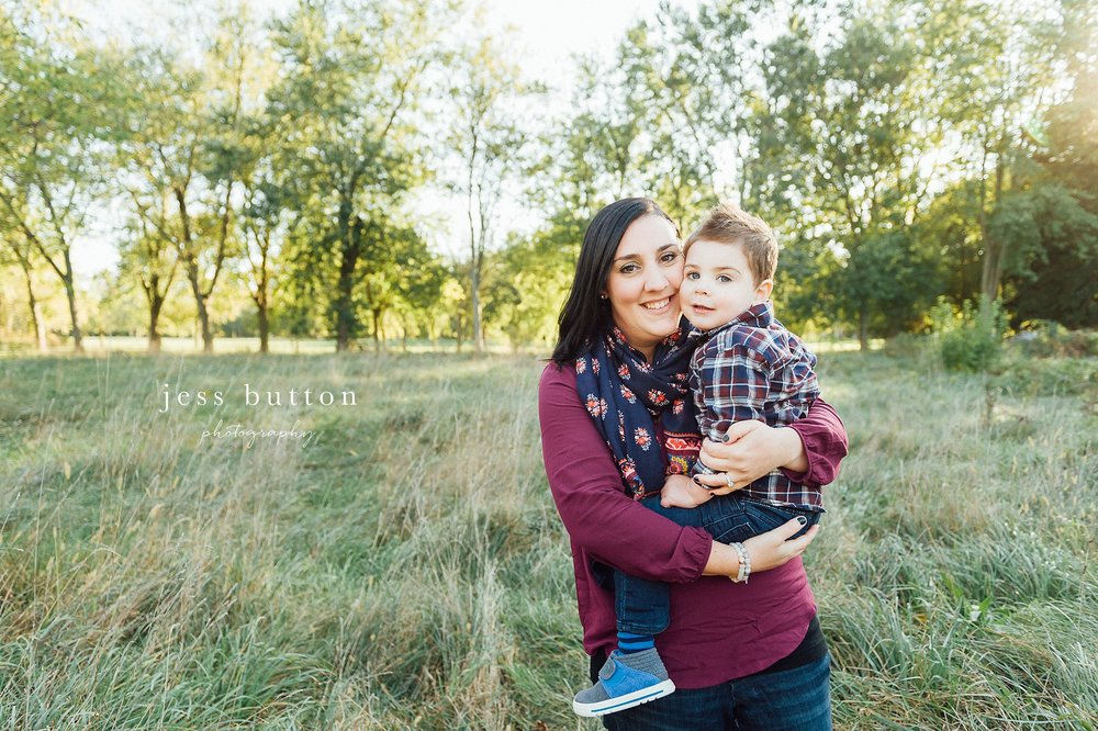Niagara Family Photographer - Fall family portraits Niagara-on-the-Lake - mom with 2 year old boy smiling in field