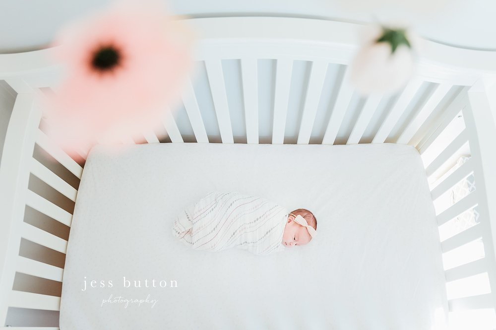 Niagara Newborn Photographer - baby girl in crib from above floral mobile