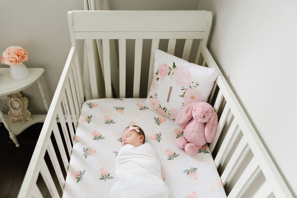 baby girl in crib with floral sheets in niagara home lifestyle photography