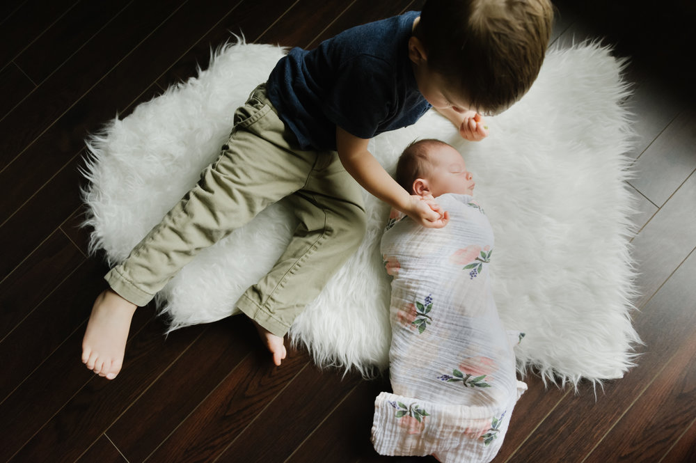 brother with newborn sister at home for newborn photographer