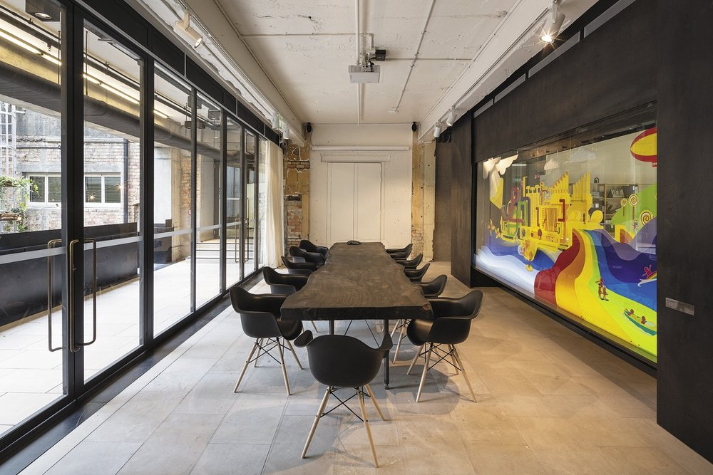 A concrete boardroom with a wooden table matched with a mural with vibrant colors
