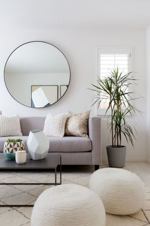 Light colour scheme with white shutter blinds. A large mirror to reflect plenty of natural light. Introducing some personality through the patterned rug and ottomans. dding a plant is a great way to break up any stark spaces.